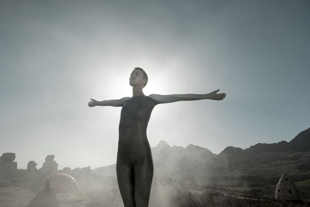 Mother, standing with outstretched arms with the sun and haze behind her.